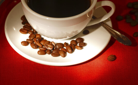 Cup of coffee and roasted coffee beans on red ground - JTF00797