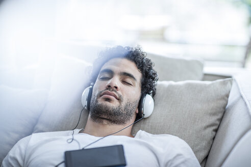 Young man relaxing on couch wearing headphones - ZEF12020