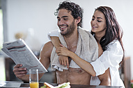 Smiling young couple at home reading newspaper - ZEF12029