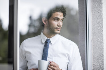 Businessman with cup of coffee looking out of window - ZEF12032