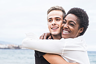 Happy young couple hugging on the beach - SIPF01208