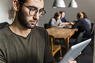 Young man using digital tablet in modern office with coworkers at table in background - TCF05284