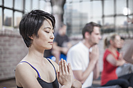 Young woman doing yoga meditaiton exercise in studio - ZEF12072