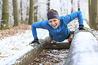Woman training on fitness trail in winter forest - VT00580