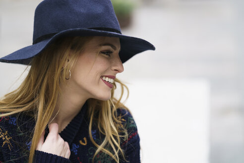 Smiling young woman wearing blue hat - KKAF00230