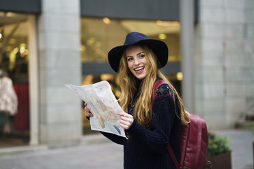 Portrait of happy tourist with city map and backpack - KKAF00233
