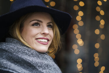 Portrait of smiling young woman wearing hat and scarf - KKAF00239