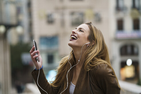 Happy young woman listening music with earphones and smartphone - KKAF00245