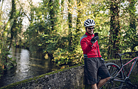 Mountain biker taking picture in forest with his smart phone - RAEF01606