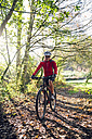 Young man mountain biking in forest - RAEF01609