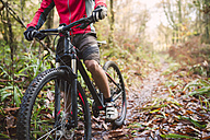 Young man mountain biking in forest - RAEF01621