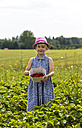 Little girl showing picked strawberries on strawberry field - JFEF00820