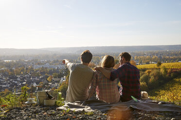 Friends sitting on a hill above a town - FMKF03359