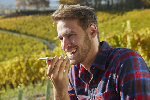 Young man in a vineyard using cell phone - FMKF03365