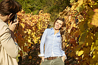 Man taking picture of young woman posing in a vineyard - FMKF03371