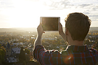 Man taking picture with a tablet on a hill above a town - FMKF03377