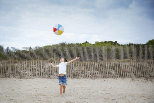 Boy on the beach throwing a colorful ball up in the air - LITF00445