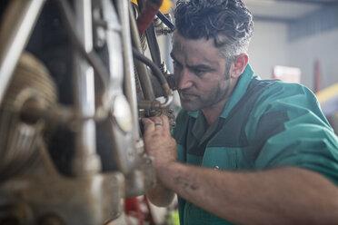 Mechanic in hangar repairing light aircraft - ZEF12139