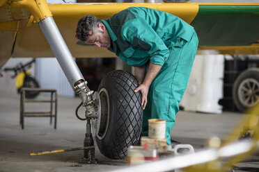Mechanic in hangar repairing light aircraft, fixing tire - ZEF12148