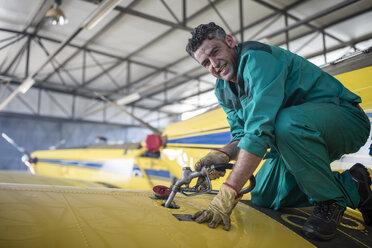 Mechanic in hangar refilling tank of light aircraft - ZEF12151
