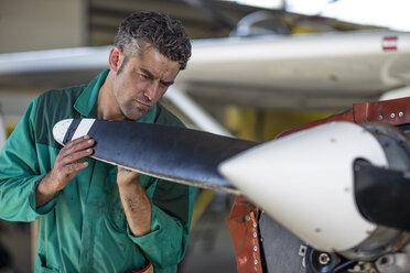 Mechanic in hangar repairing light aircraft - ZEF12157