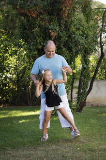 Father playing with his little daughter in the garden - LITF00469