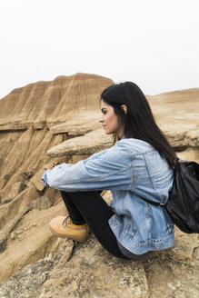 Spain, Navarra, Bardenas Reales, young woman sitting on rock in nature park looking at view - KKAF00252