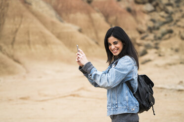 Spain, Navarra, Bardenas Reales, laughing young woman in nature park taking selfie with cell phone - KKAF00255