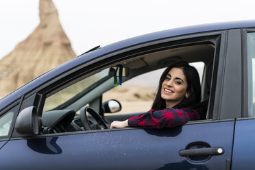 Spain, Navarra, Bardenas Reales, happy young woman looking out of car window - KKAF00261