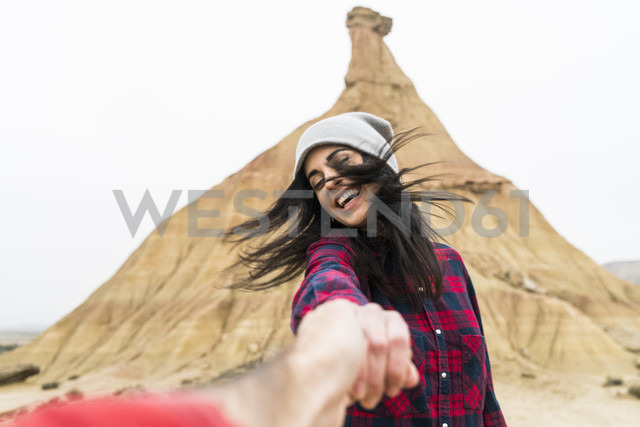 Spain, Navarra, Bardenas Reales, moving young woman holding hand of her boyfriend - KKAF00276
