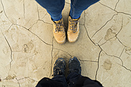 Feet of a couple standing on dried cracked ground - KKAF00285