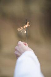 Woman's hand holding a sparkler - KKAF00288