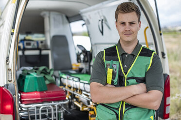 Paramedic standing with arms crossed in front of ambulance - ZEF12174