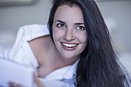 Portrait of smiling young woman with tablet in bed - ZEF12195