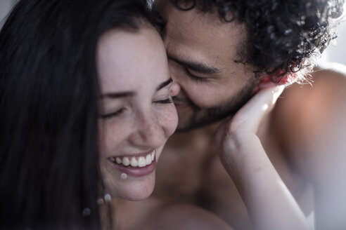 Young couple cuddling in bed - ZEF12201