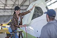 Female pilot and mechanic covering aircraft in hangar - ZEF12237