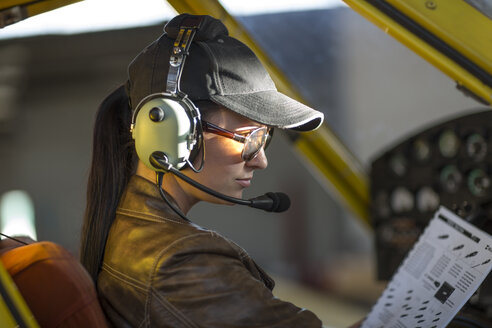 Female pilot inspecting light aircraft cockpit - ZEF12243