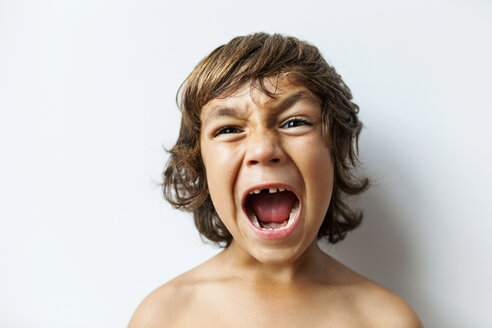 Portrait of screaming little boy with tooth gap in front of white background - VABF00974
