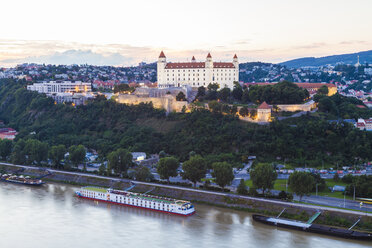 Slovakia, Bratislava, view to castle with river cruise ship on the Danube in the foreground at twilight - WDF03837