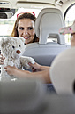 Mother looking at daughter playing with teddy bear, doing a road trip - WESTF22340