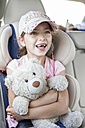 Girl sitting in car, holding teddy bear - WESTF22352