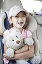 Girl sitting in car, holding teddy bear - WESTF22352