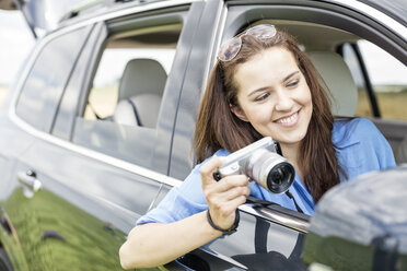 Woman sitting in car holding camera - WESTF22364