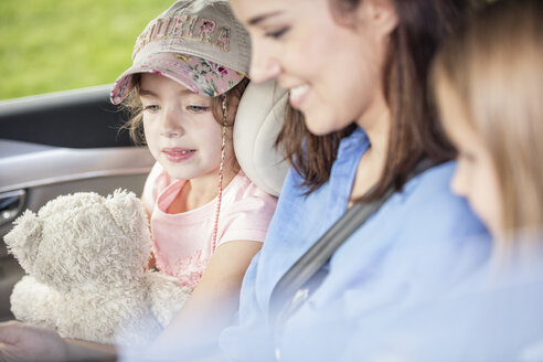 Mother and daughters on road trip sitting in car - WESTF22373