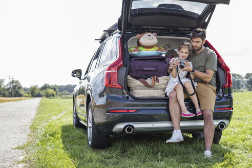 Father and daughter sitting in open car boot looking at camera at break of a road trip - WESTF22376