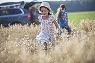 Two laughing girls running in field - WESTF22388