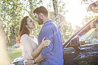 Couple embracing and kissing while on a road trip - WESTF22394