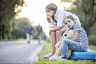 Two girls sitting on suitcase at the roadside - WESTF22400