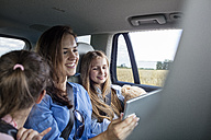 Mother and daughters on road trip sitting in car looking at digital tablet - WESTF22415