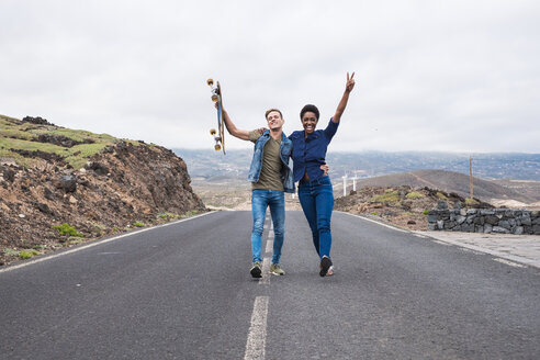Spain, Tenerife, happy young couple walking on empty road - SIPF01241